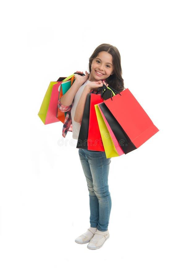 Descuentos y códigos del promo La muchacha lleva los panieres aislados en el fondo blanco Muchacha encariñada con compras Niño li foto de archivo