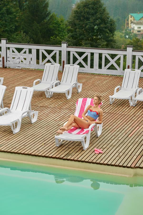 Desde arriba de la opinión la muchacha, relajándose en cubierta-silla cerca de piscina imagenes de archivo