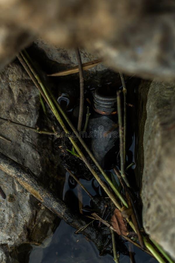 Desechos peligrosos, botellas de cristal en las rocas, contaminación ambiental imagen de archivo
