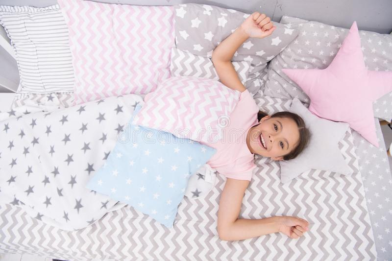 Desee su buena mañana Niño de la muchacha puesto en cama su dormitorio Niño despierto y lleno de energía El tiempo agradable rela imagenes de archivo