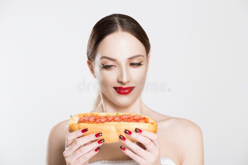 Desejando por fast food Linda jovem segurando um cachorro-quente saboroso em suas mãos, pensando em comer ou não, tendo dúvidas s imagem de stock royalty free