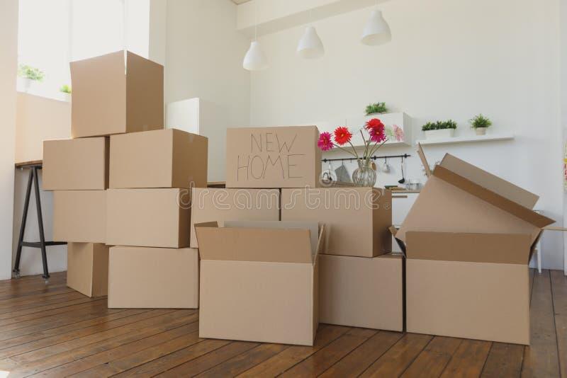 Desembalando caixas em coisas home e pondo novas afastado na cozinha, caixas de cartão grandes na casa nova Mover-se para um conc fotografia de stock royalty free