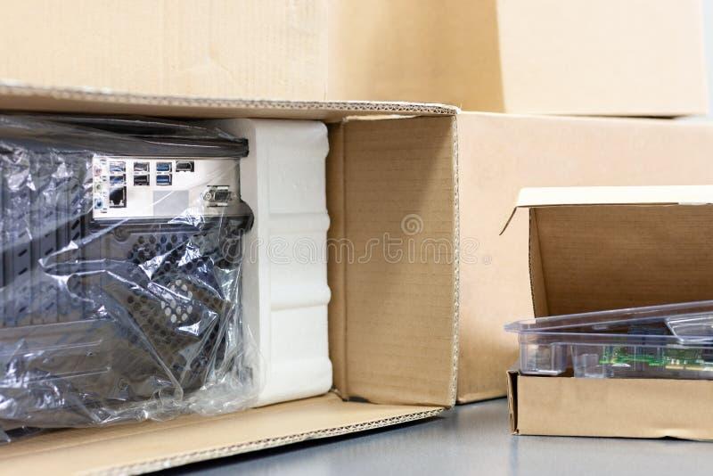 Desembalando o computador pessoal preto, vista traseira, empacotamento do celofane muitas caixas para as peças desktop do hardwar fotografia de stock
