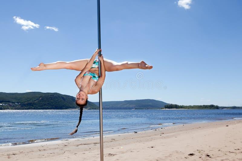 Desempenho acrobático que ri a mulher moreno no roupa de banho no polo para dançar fotos de stock