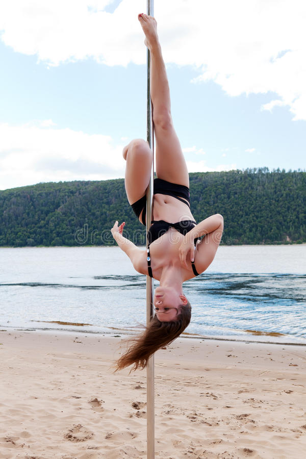 Desempenho acrobático que ri a mulher moreno no roupa de banho no polo para dançar foto de stock