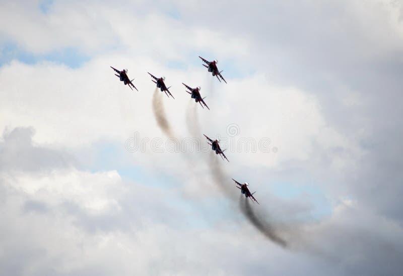 Desempenho da equipe aerobatic de Swifts nos lutadores MiG-29 altamente manobráveis de múltiplos propósitos sobre o aeródromo de  fotografia de stock royalty free