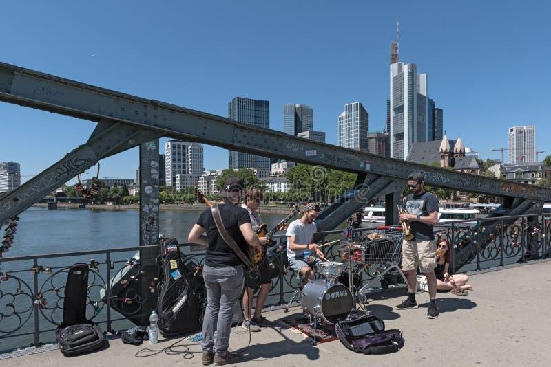 Desempenho de músicos da rua no steg do eiserner em Francoforte - são - cano principal Alemanha imagens de stock