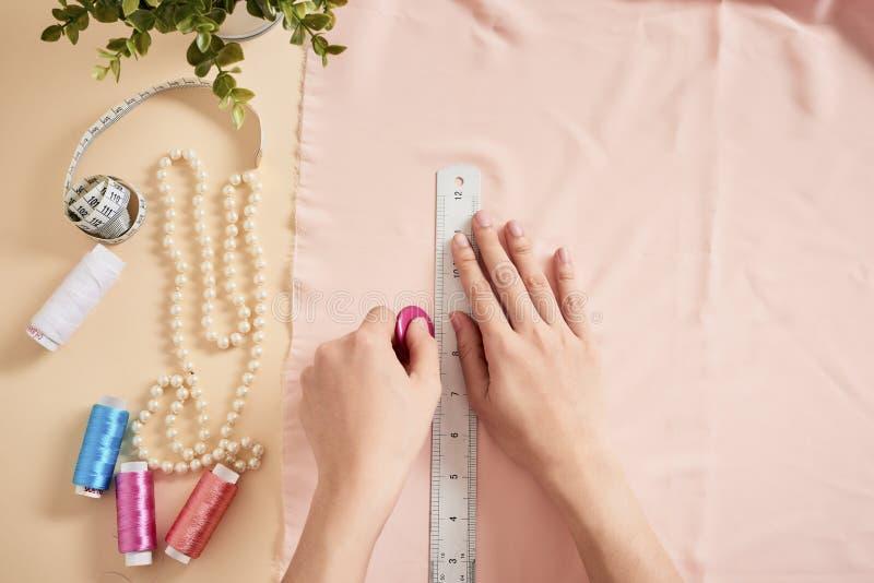 Desenhador de moda, alfaiate da mulher que levanta em seu local de trabalho com tela cortada, espaço livre na tabela Indústria de imagens de stock
