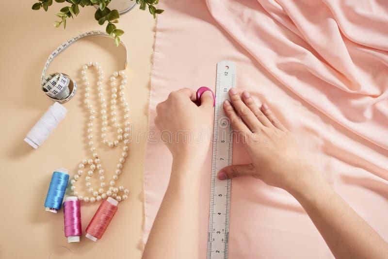 Desenhador de moda, alfaiate da mulher que levanta em seu local de trabalho com tela cortada, espa?o livre na tabela Ind?stria de foto de stock royalty free
