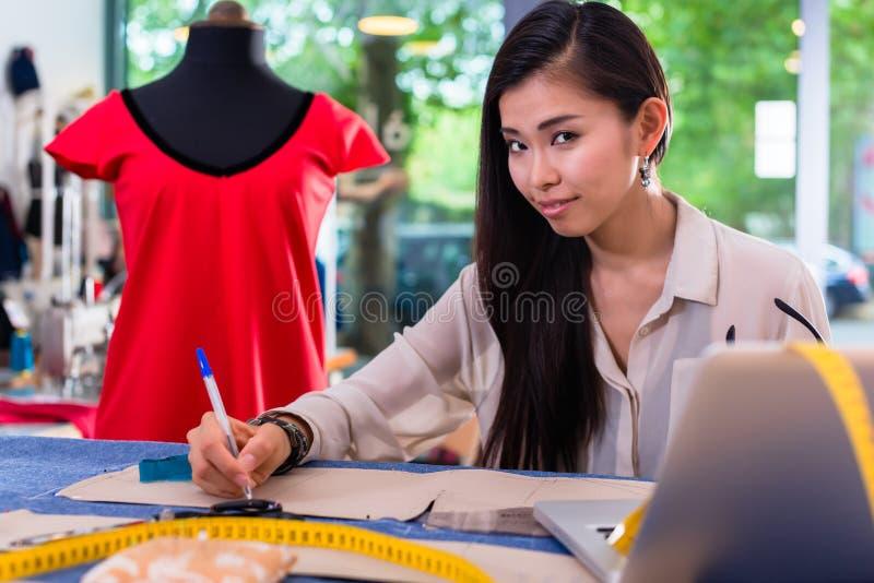 Desenhador de moda asiático que prepara esboços para entalhes imagem de stock