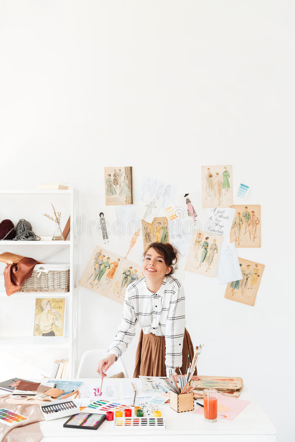 Desenhador de moda de sorriso da jovem mulher que está em seu local de trabalho fotografia de stock