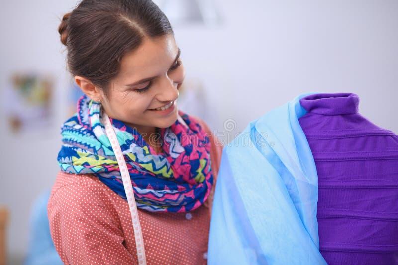 Desenhador de moda de sorriso que está o manequim próximo imagens de stock royalty free