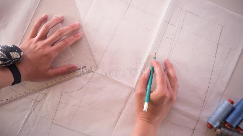 Desenhador de moda fêmea que trabalha com corte do teste padrão no estúdio imagem de stock royalty free