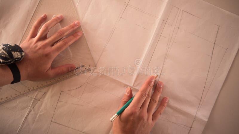 Desenhador de moda fêmea que trabalha com corte no estúdio, vista superior do teste padrão fotos de stock