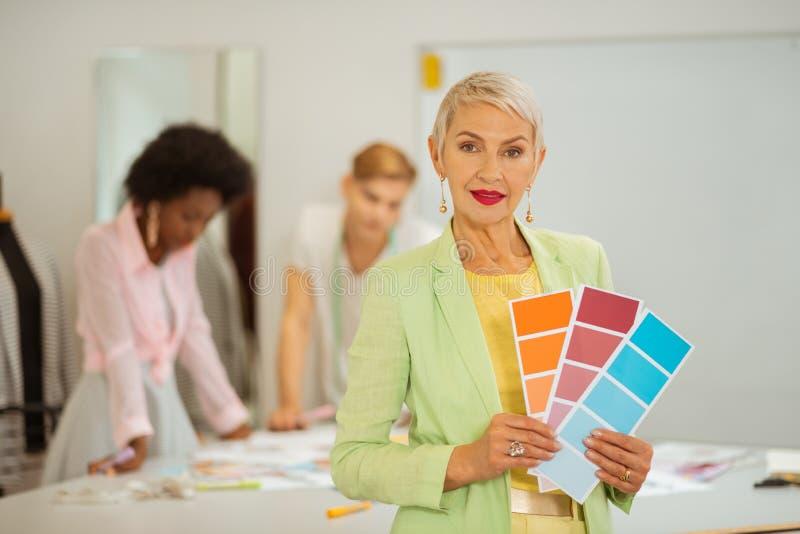 Desenhador de moda fêmea superior que guarda amostras da cor fotos de stock