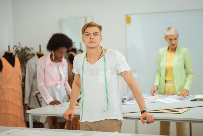 Desenhador de moda masculino novo considerável que está com seus colegas fotografia de stock royalty free