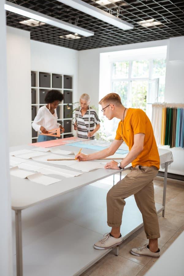 Desenhador de moda masculino novo ocupado que trabalha com colegas imagens de stock