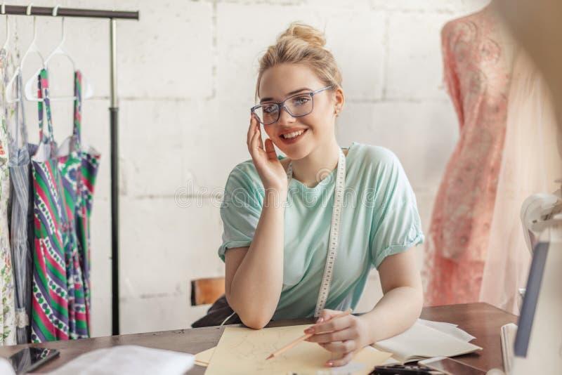 Desenhador de moda no trabalho Esboço do desenho da costureira de Talanted em seu espaço de trabalho imagem de stock royalty free