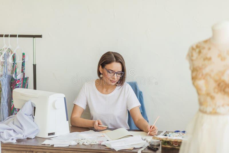 Desenhador de moda no trabalho Esboço do desenho da costureira de Talanted em seu espaço de trabalho imagens de stock