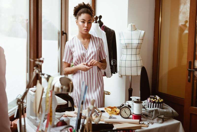 Desenhador de moda novo no local de trabalho, mulher africana que olha à câmera fotos de stock