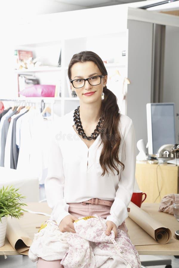 Desenhador de moda novo que trabalha em seu estúdio fotografia de stock