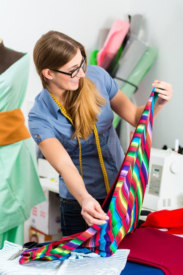 Desenhador de moda ou alfaiate que trabalham no estúdio fotografia de stock