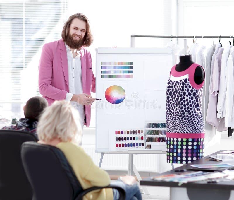 Desenhador de moda que mostra a colegas a paleta de cores para a coleção nova imagens de stock