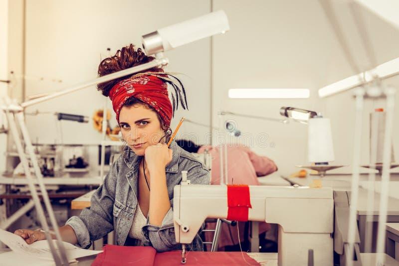 Desenhador de moda que senta-se em sua mesa e que olha de sobrancelhas franzidas imagem de stock royalty free