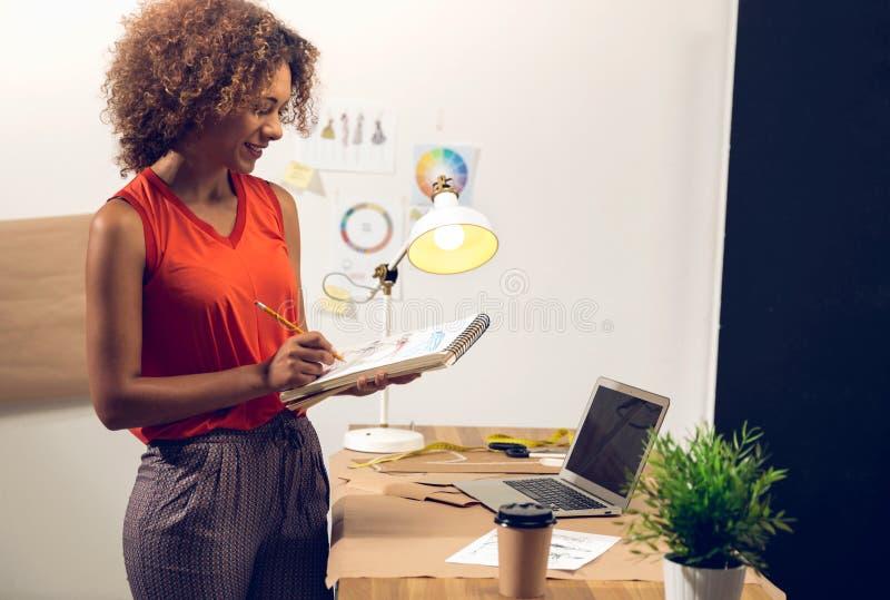 Desenhador de moda que trabalha em sua oficina foto de stock