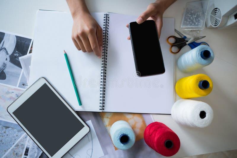 Desenhador de moda que usa o telefone celular na mesa foto de stock royalty free