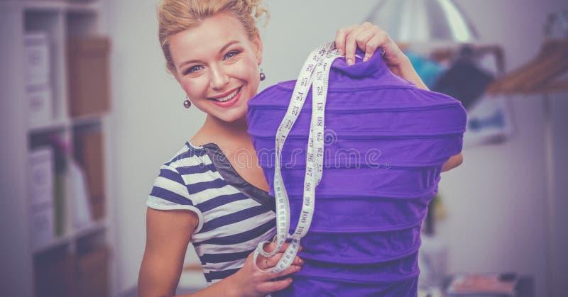 Desenhador de moda de sorriso que está o manequim próximo no escritório fotografia de stock royalty free