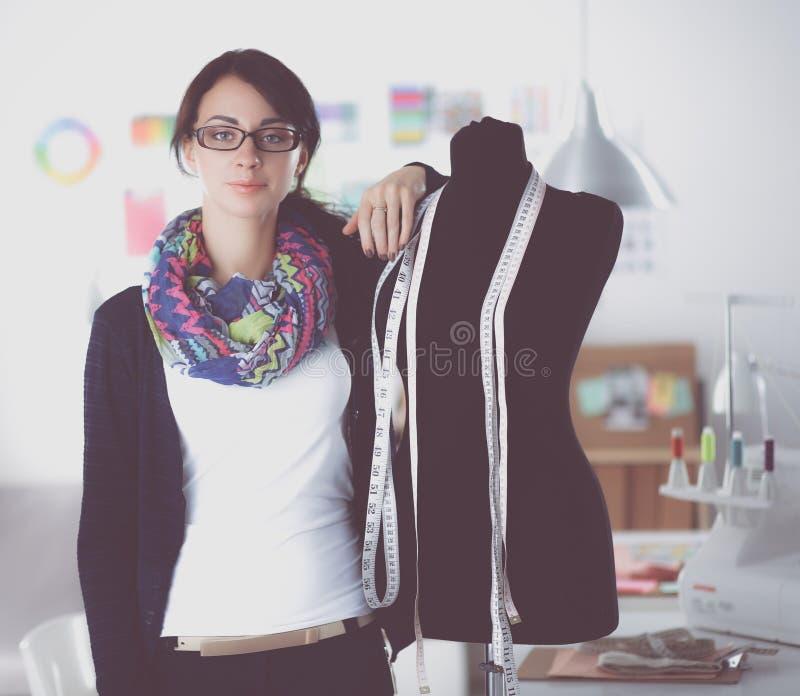 Desenhador de moda de sorriso que está o manequim próximo no escritório imagens de stock