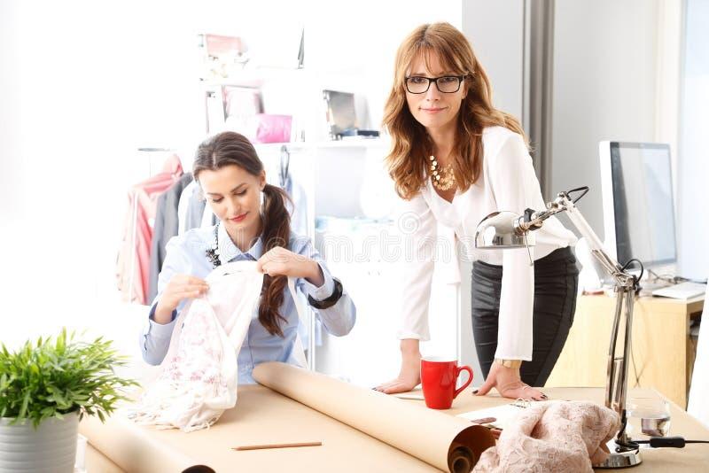 Desenhadores de moda bonitos que trabalham junto no estúdio. fotografia de stock royalty free