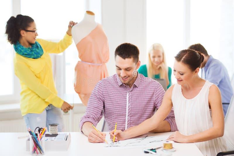 Desenhadores de moda de sorriso que trabalham no escritório foto de stock royalty free