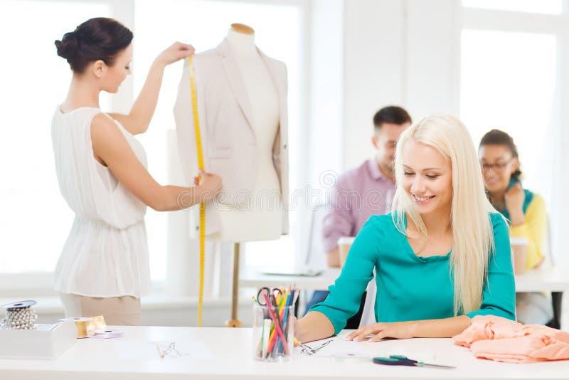Desenhadores de moda de sorriso que trabalham no escritório fotografia de stock royalty free