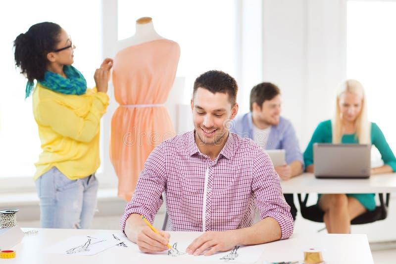 Desenhadores de moda de sorriso que trabalham no escritório imagem de stock royalty free
