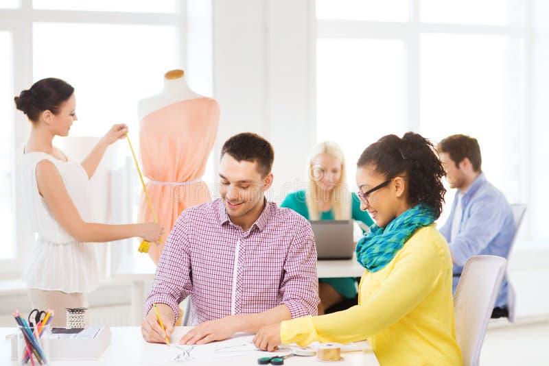 Desenhadores de moda de sorriso que trabalham no escritório imagem de stock