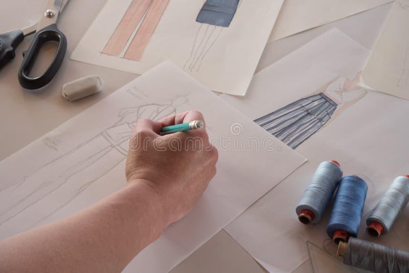 Desenhadores de moda fêmeas que tiram esboços para a roupa na oficina imagem de stock royalty free