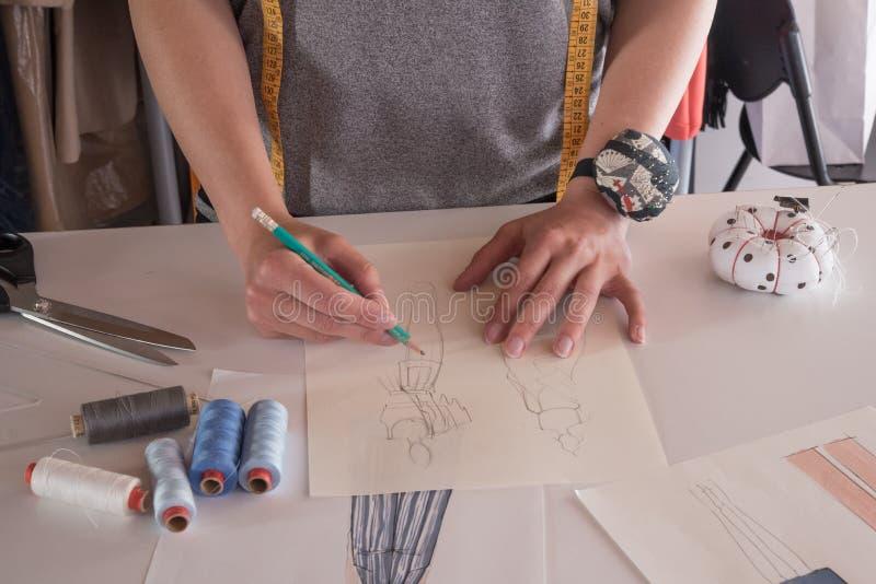 Desenhadores de moda fêmeas que tiram esboços para a roupa na oficina imagens de stock royalty free
