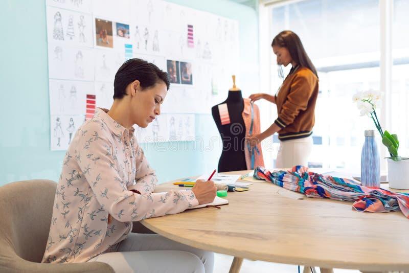 Desenhadores de moda fêmeas que trabalham em um escritório moderno foto de stock