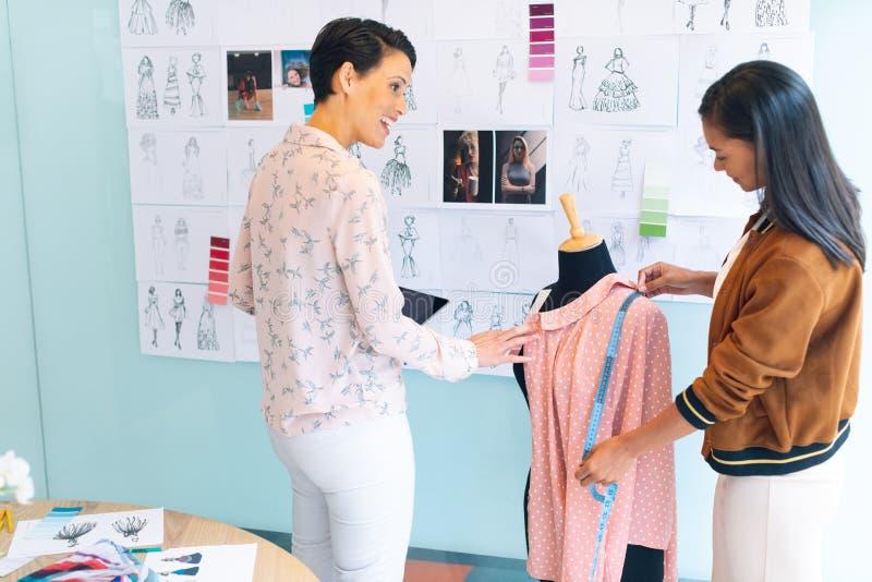 Desenhadores de moda fêmeas que trabalham junto o trabalho no vestuário no modelo de costureira fotos de stock royalty free