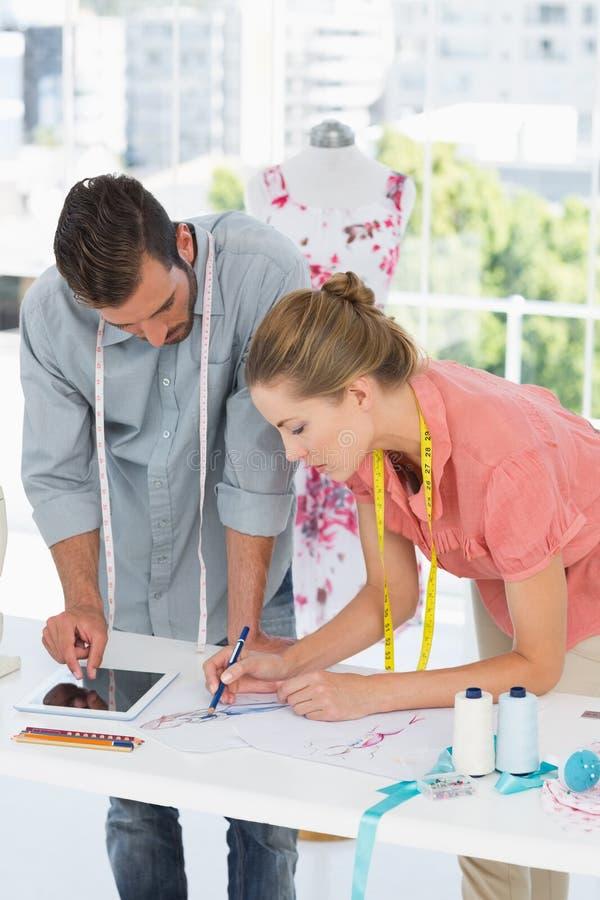 Desenhadores de moda no trabalho no estúdio brilhante imagens de stock