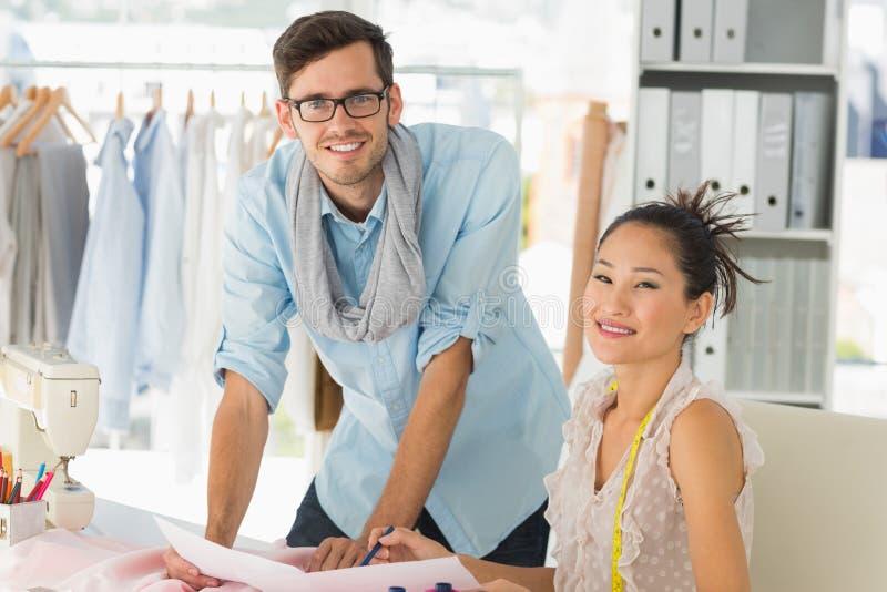 Desenhadores de moda no trabalho no estúdio brilhante imagem de stock