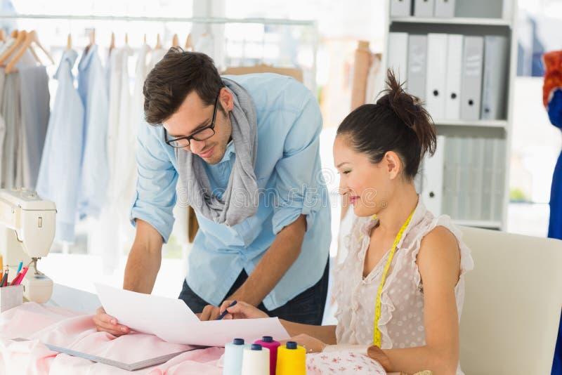 Desenhadores de moda no trabalho no estúdio brilhante foto de stock