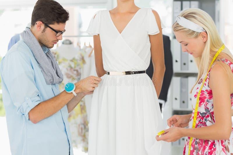 Desenhadores de moda que ajustam o vestido no modelo foto de stock royalty free