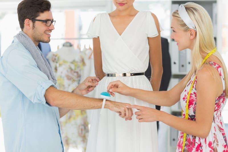 Desenhadores de moda que ajustam o vestido no modelo fotos de stock royalty free