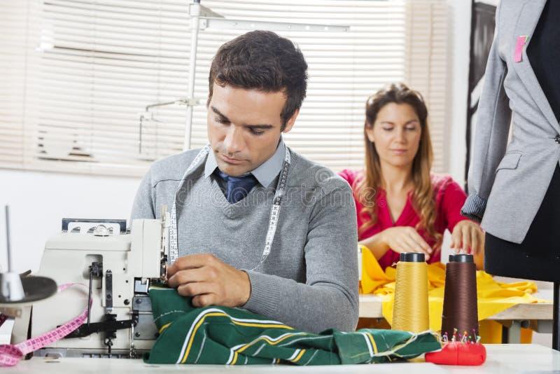 Desenhadores de moda que costuram telas na fábrica da costura imagem de stock