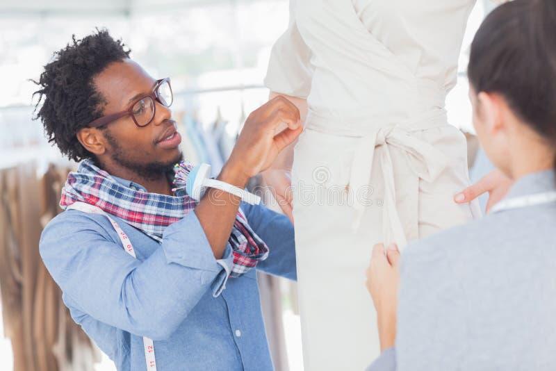 Desenhadores de moda que estão ao lado de um modelo fotografia de stock