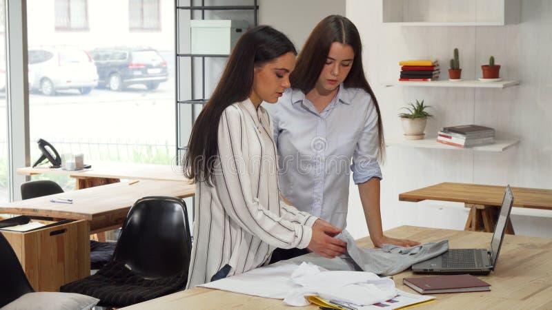 Desenhadores de moda que examinam t-shirt em sua oficina imagens de stock royalty free