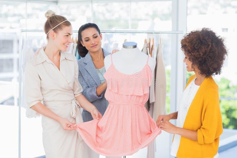 Desenhadores de moda que olham um vestido imagens de stock